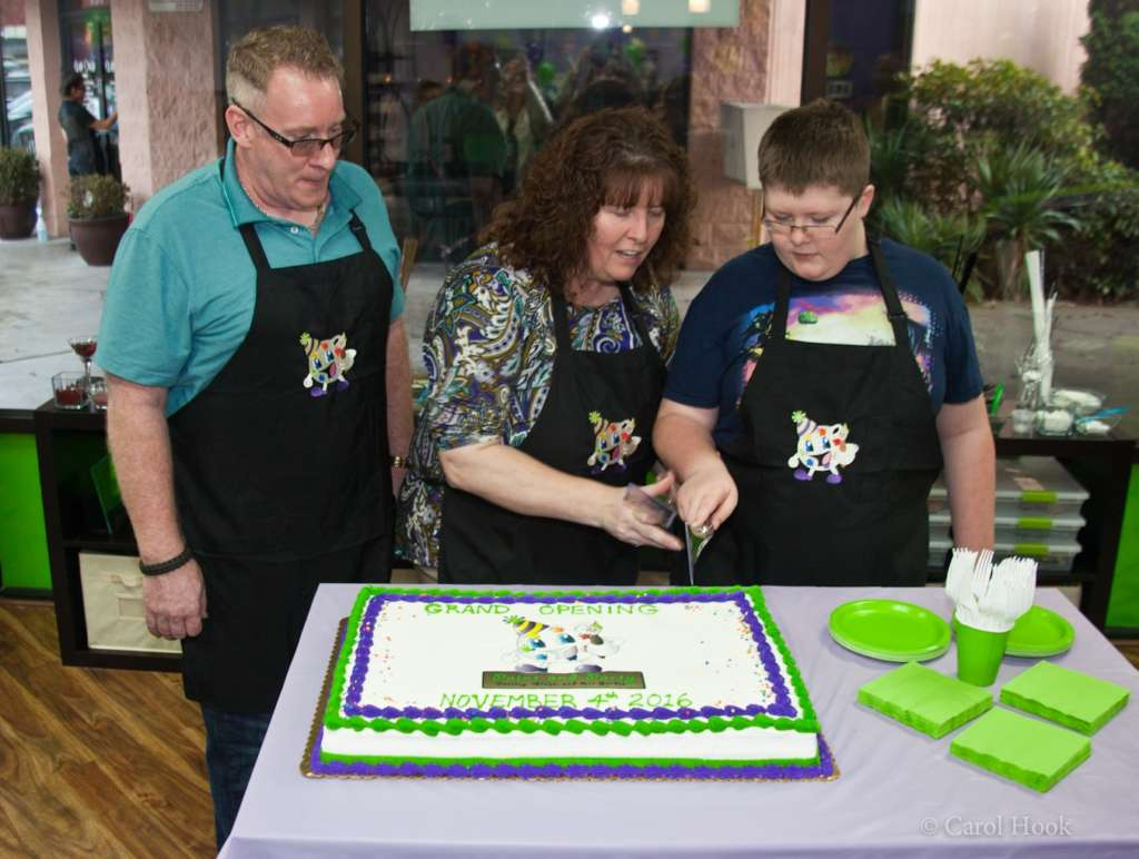 Tim & Lisa Nielsen, with their son, cut the cake, for the grand opening at Paint & Party!